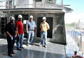 Rodi Marine representatives examine the first of two 175-foot fast supply vessels that Swiftships is building for the Lafayette company. This one is expected to be completed in April with a second ready for delivery in July. From left, are Zeke Randaza, Wade Guillory and Timmy Charpentier, all of Rodi Marine, along with Swiftships project manager Allen Crochet.