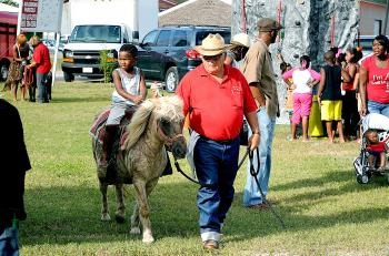 """The third annual Hoodstock event was held Saturday on 11th Street at La. 182 in Morgan City. Among the features were rides, music and speakers. Jadyn Gibson, 3, of Morgan City, rides a pony named """"Linda"""" accompanied by Jorge Gomez of AGA Farm Pony Rides in Covington."""