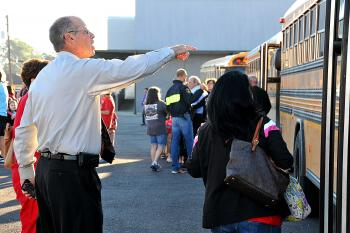 Assistant Superintendent of St. Mary Parish Schools helps to direct children and faculty of Wyandotte Elementary School  onto buses this morning during a mandatory evacuation.
