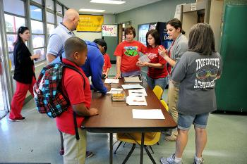Parents and children of Wyandotte Elementary School check in at Morgan City Junior High School this morning  after an evacuation following a gas line leak near their school relocated them.