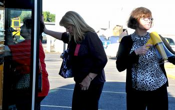 Principal of Wyandotte Elementary School directs a steady flow of people from Charlies Lanes parking lot onto buses this morning following a mandatory evacuation. Students were relocated to the nearby parking lot as a safety measure until buses later brought them to Morgan City Junior High School.