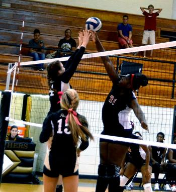 Patterson's Arian Grogan hits a shot, while Berwick's Abigail Askew defends and fellow Lady Panther Ashton Morales looks on during the squads' district matchup Tuesday. Berwick came away with the home win in straight sets.