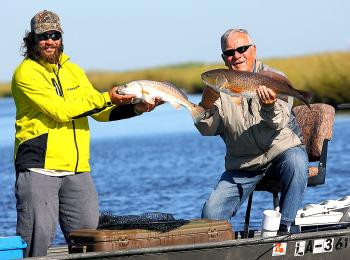 Book author Jake Bussolini, right, from North Carolina with his Grosse Savanne Guide and a red fish the angler caught during a media saltwater fishing trip at the Southeastern Outdoor Press Association annual conference in Lake Charles last weekend.