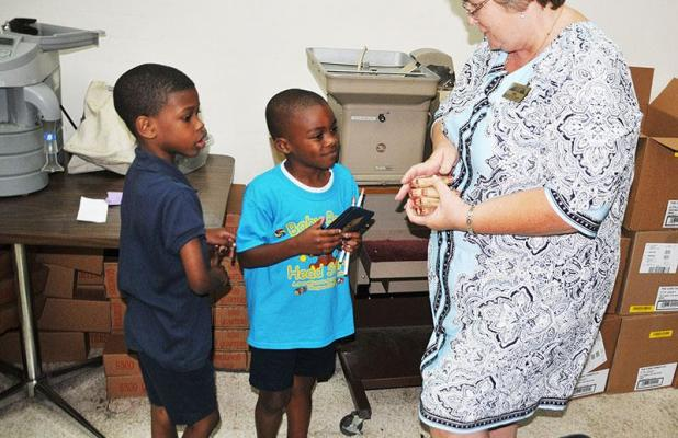 Baby Bear Head Start students Zane Minor, left, and Kayson Span look on as  Melonia Giroir, M C Bank Colonial Plaza branch manager, shows them rolls of  coins ...